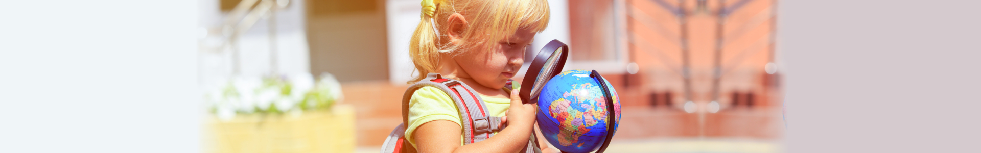 beautiful little girl holding a magnifying glass and a globe